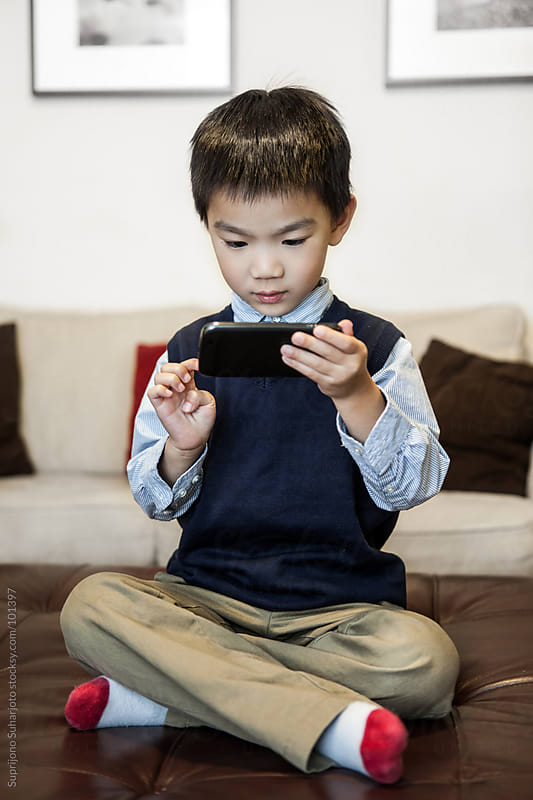 Asian boy playing game at home on the cell phones  by Suprijono Suharjoto for Stocksy United