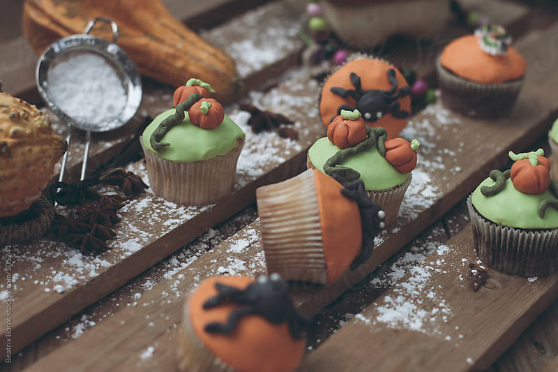 Halloween theme decorated cupcakes with powdered sugar on a table  by Beatrix Boros for Stocksy United