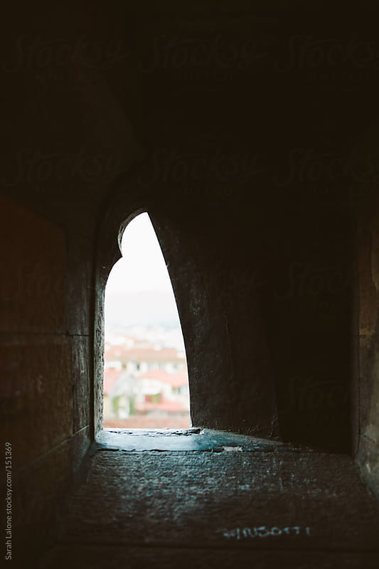 view out of small stone windows in the duomo in florence by Sarah Lalone for Stocksy United