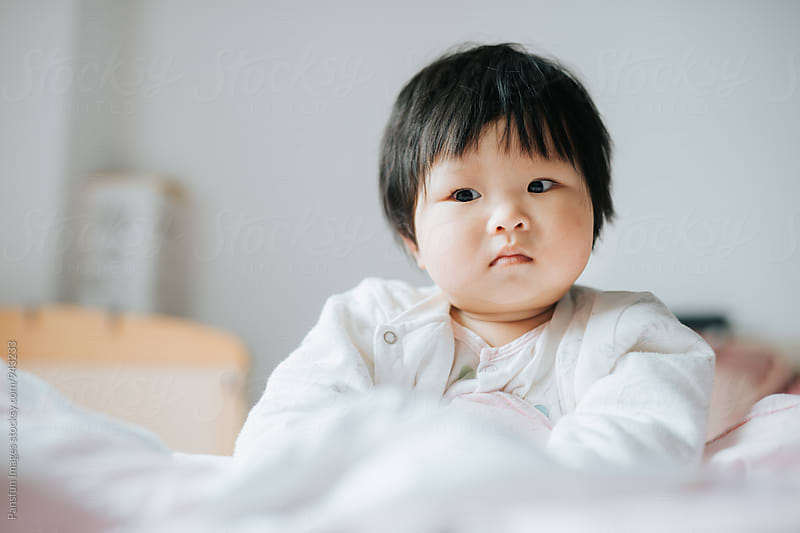 baby girl on bed by Pansfun Images for Stocksy United