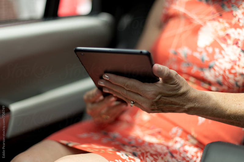 Elderly woman looking at her tablet in the car by Eddie Pearson for Stocksy United