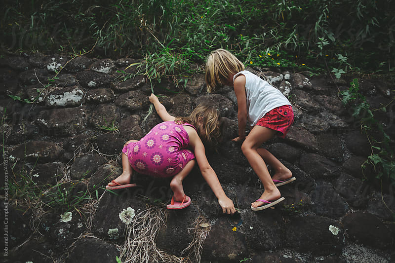 Brave young sisters climbing rock wall in summer by Rob and Julia Campbell for Stocksy United