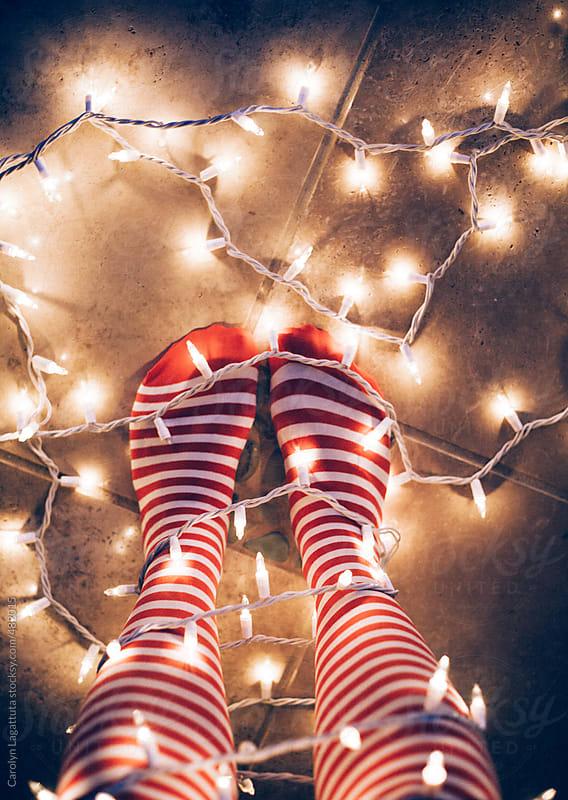 Striped knee high socks and Christmas lights by Carolyn Lagattuta for Stocksy United