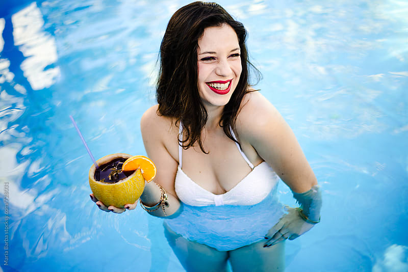 Young brunette girl having a cocktail at the pool by María Barba for Stocksy United