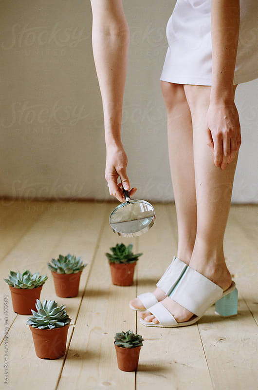 Woman watching her shoes with magnifying glass by Lyuba Burakova for Stocksy United