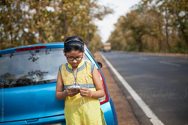 A girl using smartphone beside National Highway,India by PARTHA PAL for Stocksy United