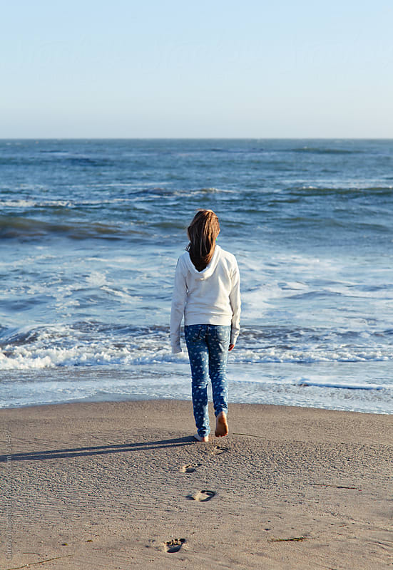 Young girl standing in front of the ocean - looking out. by Carolyn Lagattuta for Stocksy United