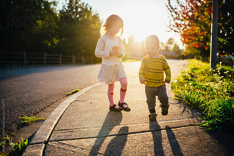 Young sister and baby brother walk along the side of the road in the bold light of the setting sun by Amanda Voelker for Stocksy United