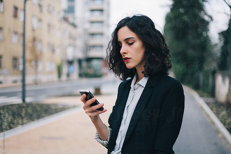 Beautiful woman in suit using her mobile phone  by Marija Mandic for Stocksy United