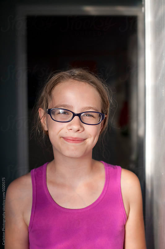 Smiling girl in doorway by Carleton Photography for Stocksy United