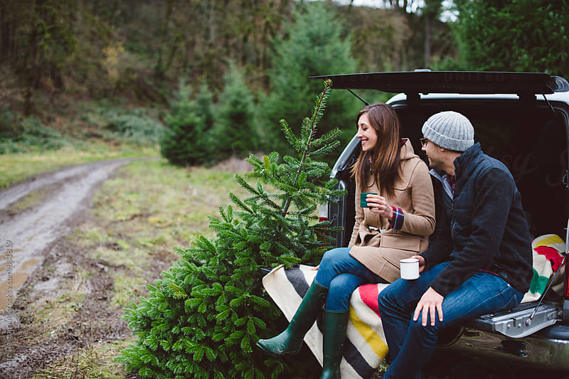 Couple sitting on the tailgate of a truck after cutting down their Christmas tree. by Kate Daigneault for Stocksy United