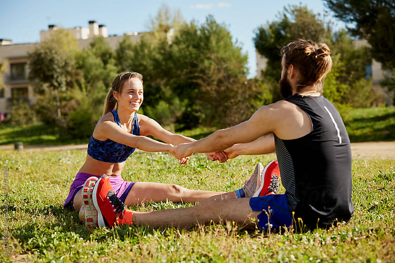 Runners Holding Hands While Stretching Seated Forward Bend On Grass by ALTO IMAGES for Stocksy United
