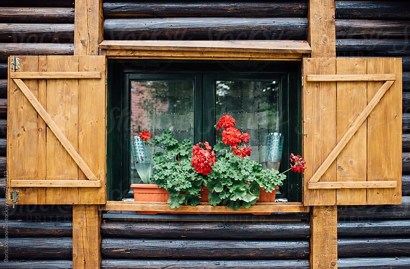 Window of the wooden cabin in the house by Boris Jovanovic for Stocksy United