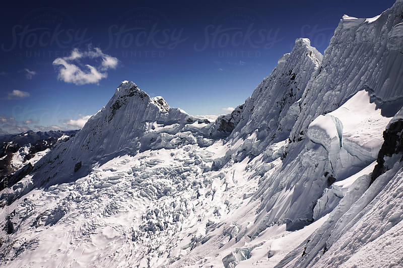 Ice and snow-covered mountain peaks seen from high altitude by Mick Follari for Stocksy United