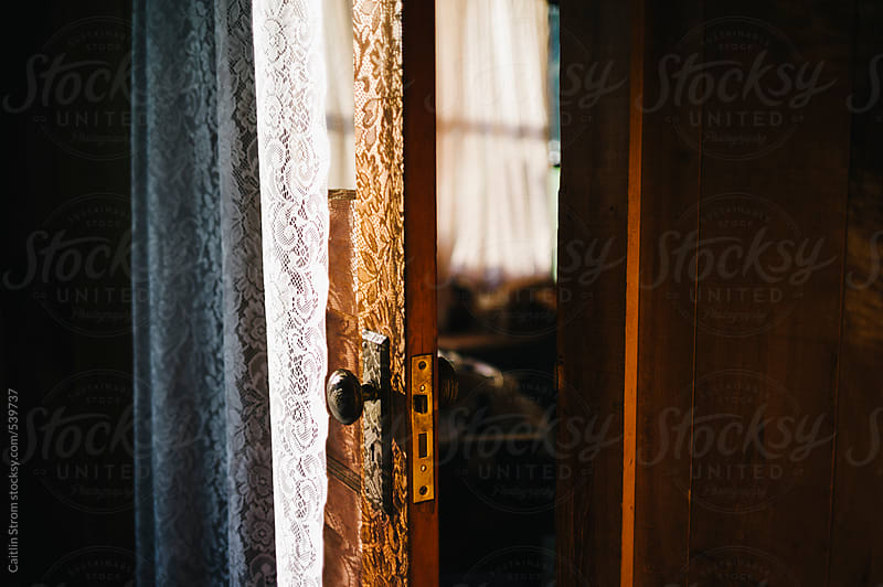 lace curtain on a door by Caitlin Strom for Stocksy United