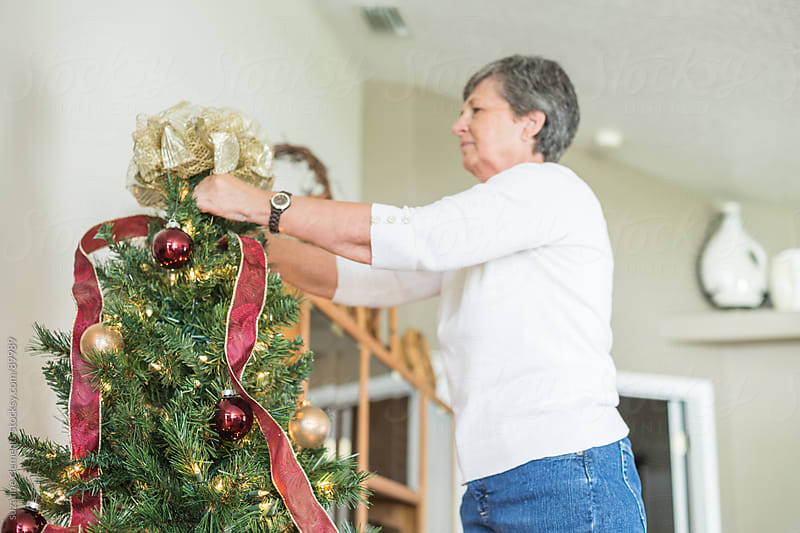 Woman Decorates her Christmas Tree by suzanne clements for Stocksy United