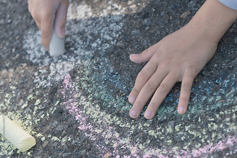 child drawing with chalk on the pavement by Gillian Vann for Stocksy United