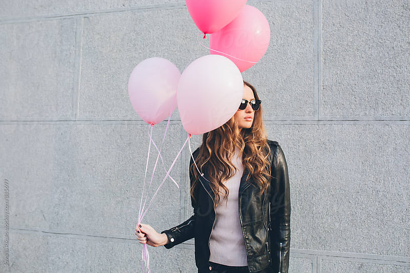 Young woman holding colorful pink balloons by Jovana Rikalo for Stocksy United