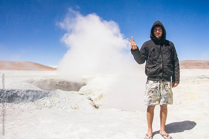 Adult man showing peace sign to camera against of geyser by Alejandro Moreno de Carlos for Stocksy United