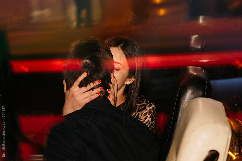Young lovers kissing in party bus by Beatrix Boros for Stocksy United