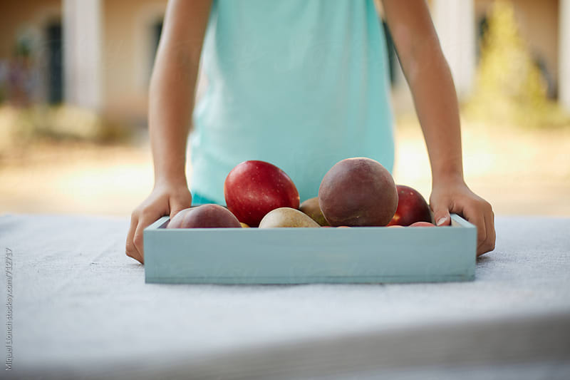 Close up of a child with with a tray full of fresh fruit by Miquel Llonch for Stocksy United