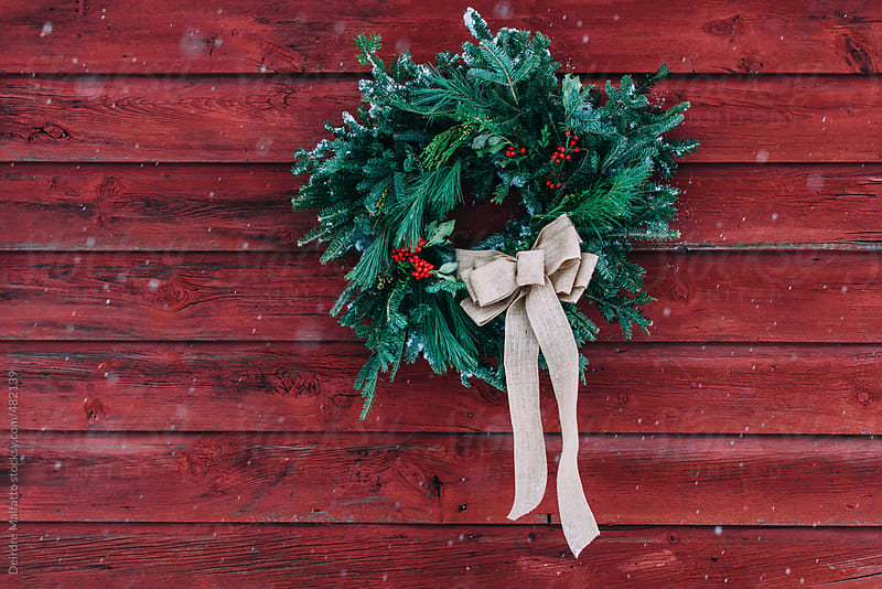 christmas wreath on a red barn wall by Deirdre Malfatto for Stocksy United