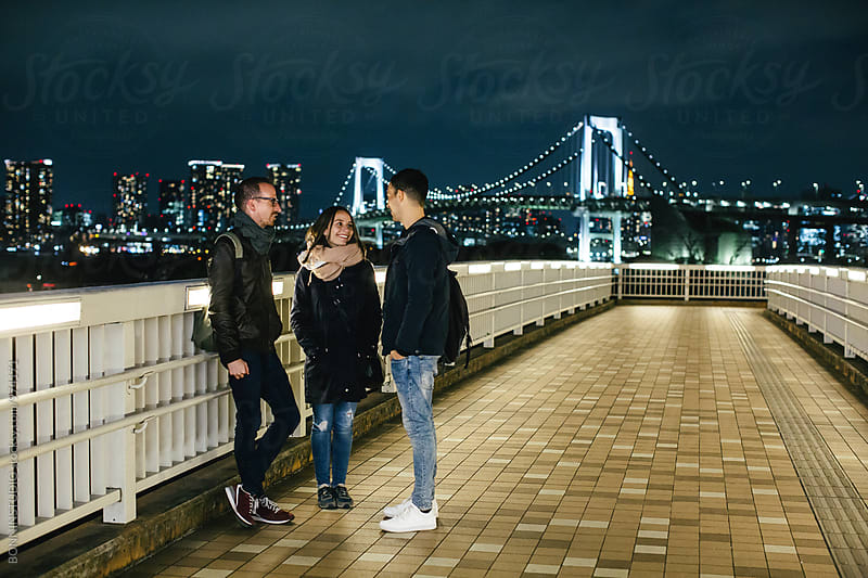 Tourist friends chatting in Tokyo cityscape at night. by BONNINSTUDIO for Stocksy United