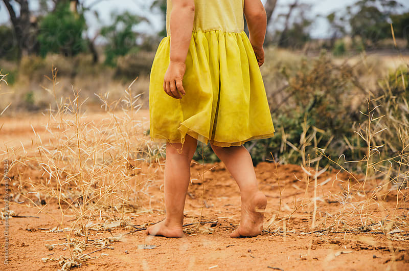 Little girl walking in the outback barefoot by Dominique Chapman for Stocksy United