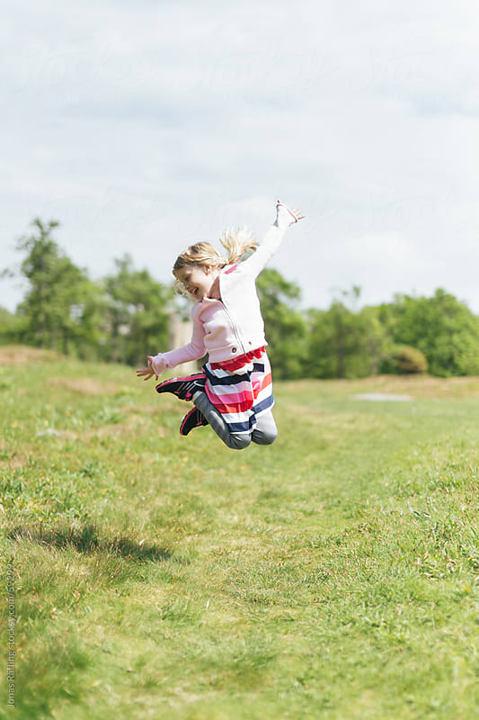 Young girl is jumping with joy by Jonas Räfling for Stocksy United