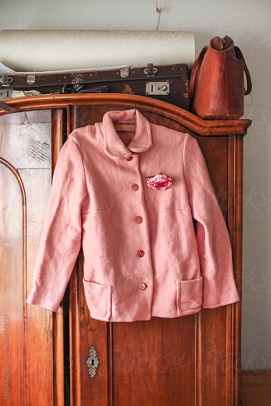 Pink jacket hanging on the closet by Marija Kovac for Stocksy United