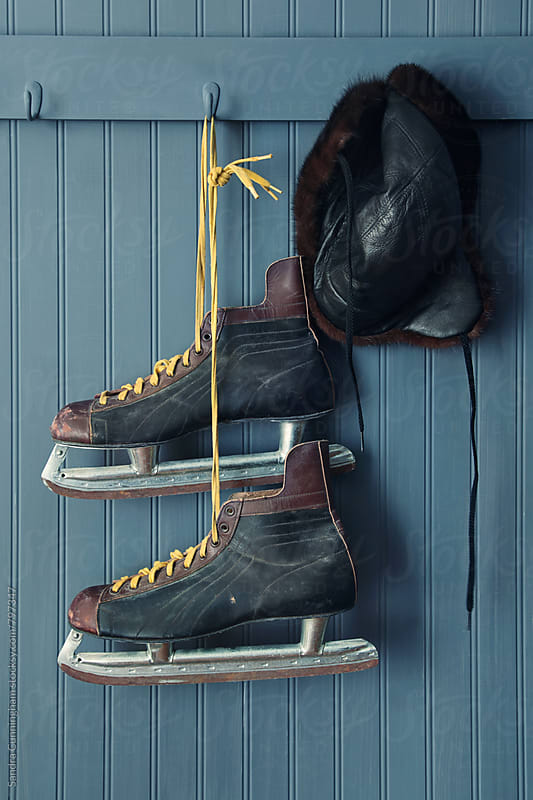 Closeup of vintage men's skates and hat on hooks by Sandra Cunningham for Stocksy United