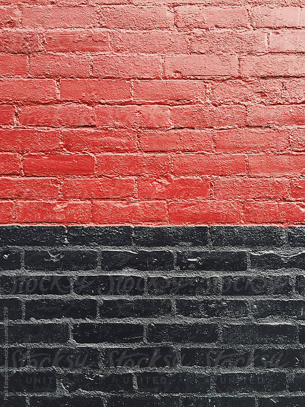 Painted red and black brick wall by Paul Edmondson for Stocksy United