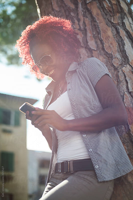 Black young woman using a phone outdoors by GIC for Stocksy United