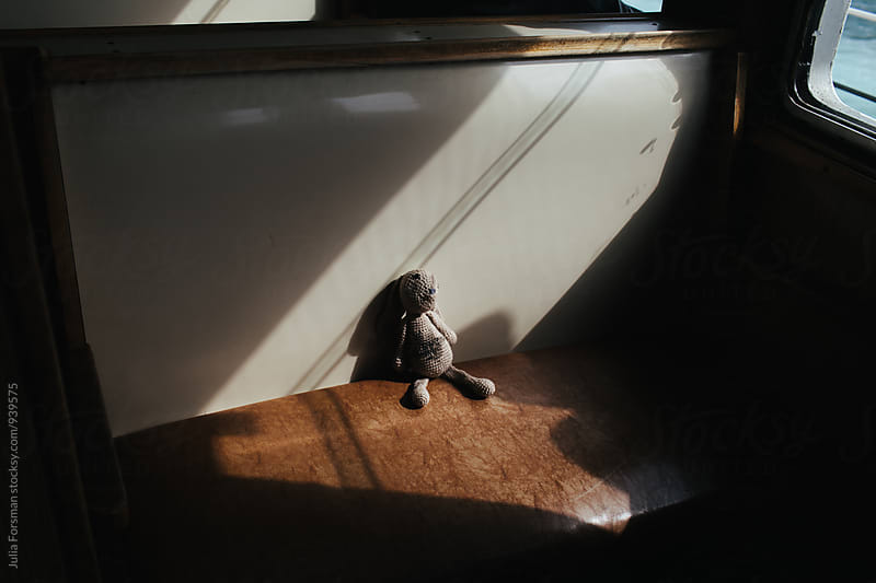 A worn and loved handmade rabbit toy sits in a shaft of sunlight on a traditional Istanbul ferryboat. by Julia Forsman for Stocksy United
