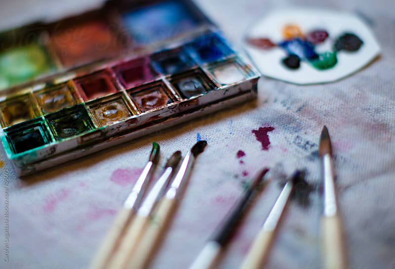 Paint palette, brushes and a canvas by Carolyn Lagattuta for Stocksy United