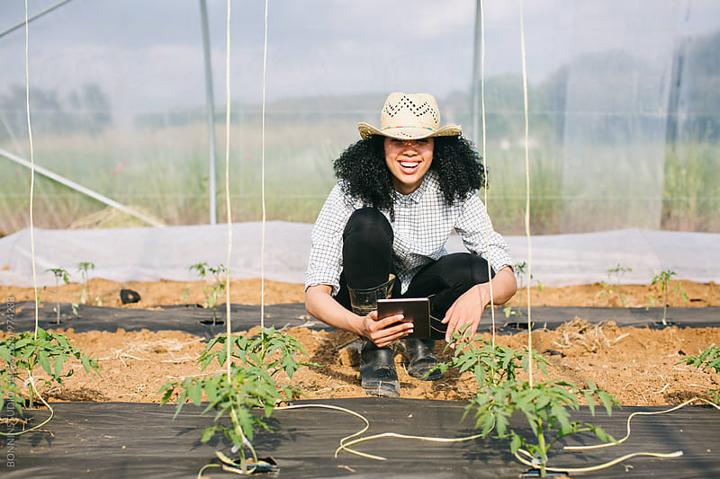 Smiling woman using a digital tablet in a greenhouse. by BONNINSTUDIO for Stocksy United