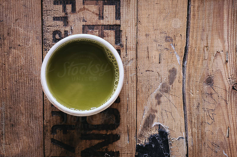 Cup of Matcha Tea placed on a Wooden Board. by Claudia Lommel for Stocksy United
