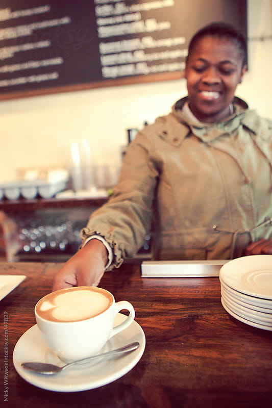 African woman serving coffee in a restaurant by Micky Wiswedel for Stocksy United