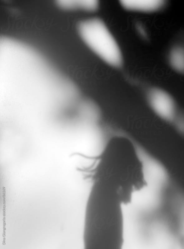 Shadow on the wall of a tree and silhouette of girl with hair blowing by Dina Giangregorio for Stocksy United