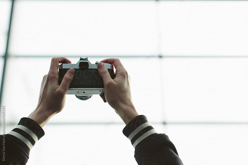 Two arms holding camera up in the air by Denni Van Huis for Stocksy United