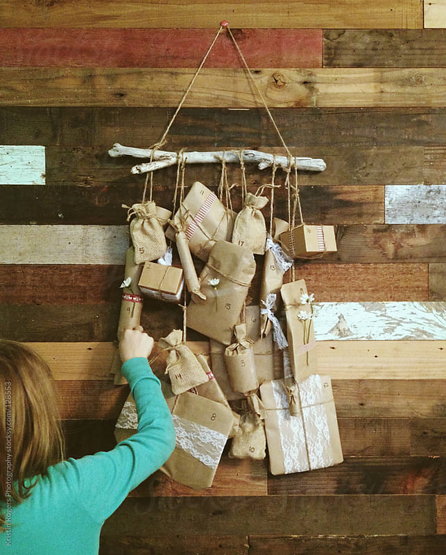 young girl picks her gift on homemade advent calendar  by Kristin Rogers Photography for Stocksy United