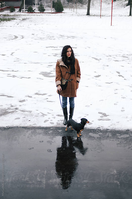 Brunette woman with her black dog outdoor  by Marija Kovac for Stocksy United