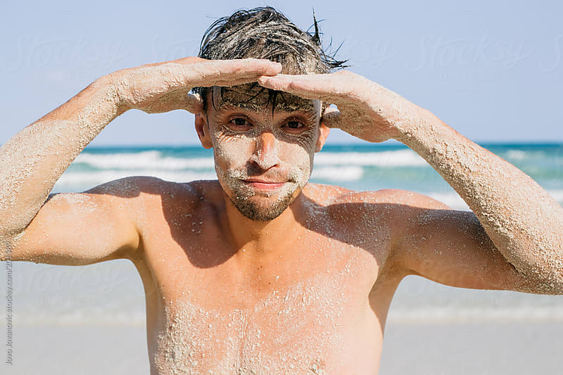 Man covered with sand looking at the camera by Jovo Jovanovic for Stocksy United