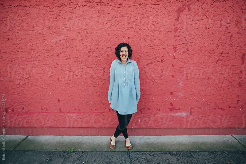 Young happy woman standing near pink red wall outside by Rob and Julia Campbell for Stocksy United