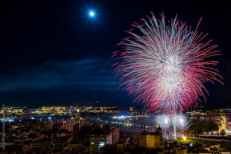 a city landscape with fireworks celebration by Javier Pardina for Stocksy United