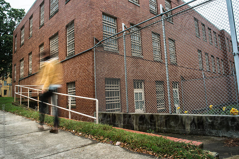 Urban Woman Touring Fenced Abandoned Psychiatric Facility by Brian McEntire for Stocksy United