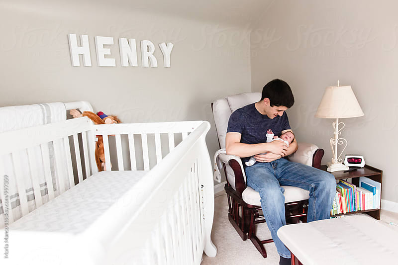 dad holds newborn baby in nursery by Maria Manco for Stocksy United