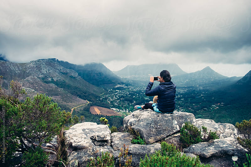 Female hiker taking a photo of a stormy mountain view with her cell phone by Micky Wiswedel for Stocksy United