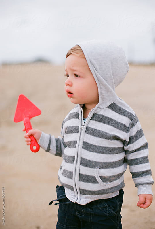 Cute young boy with hoodie playing on the beach with a shovel by Jakob for Stocksy United