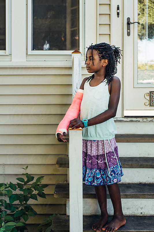 Black girl with a pink cast standing on the steps by Gabriel (Gabi) Bucataru for Stocksy United
